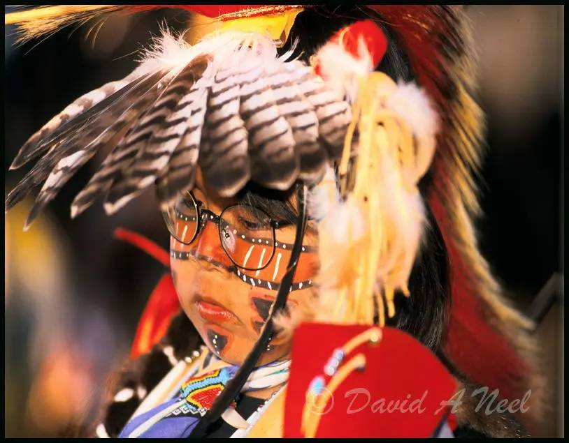 A young Native boy with Traditional dance headress and face paint.