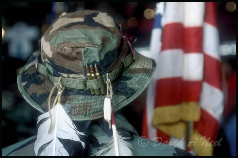 Native American war veteran carries the colors.