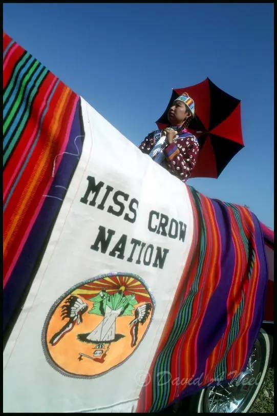 Miss Crow Nation stays out of the sun as she rides in a parade at Crow Fair.