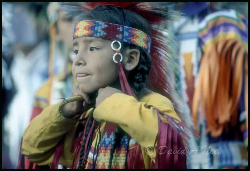 A young Native boy concentrates on getting dressed to dance.