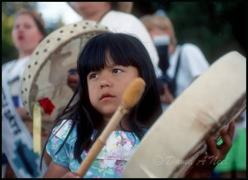 A Native American girl with a hand drum.