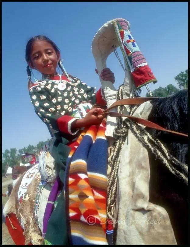 Crow girl wearing an elk-tooth dress on horseback.