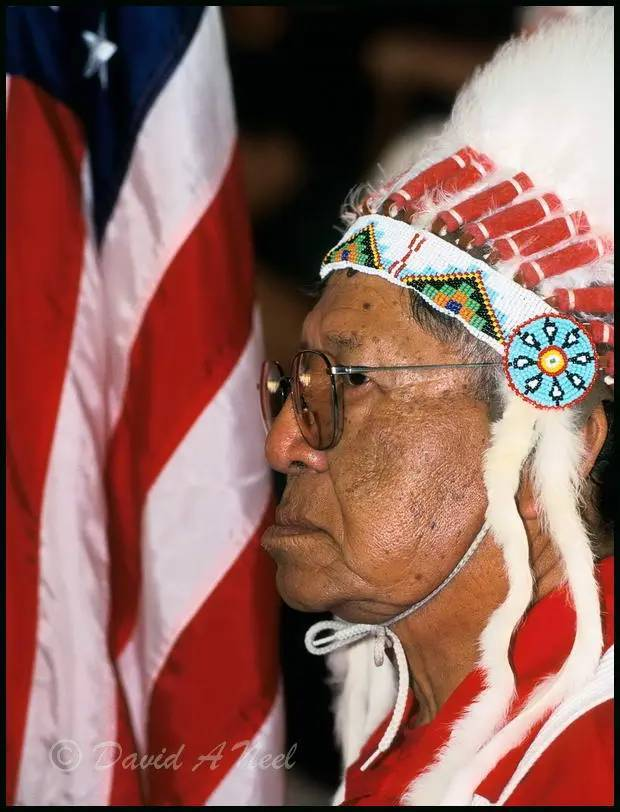 A Native American chief carries the American flag in a Grand Entry ceremony.