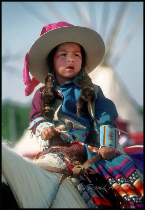 Native American boy on horseback.