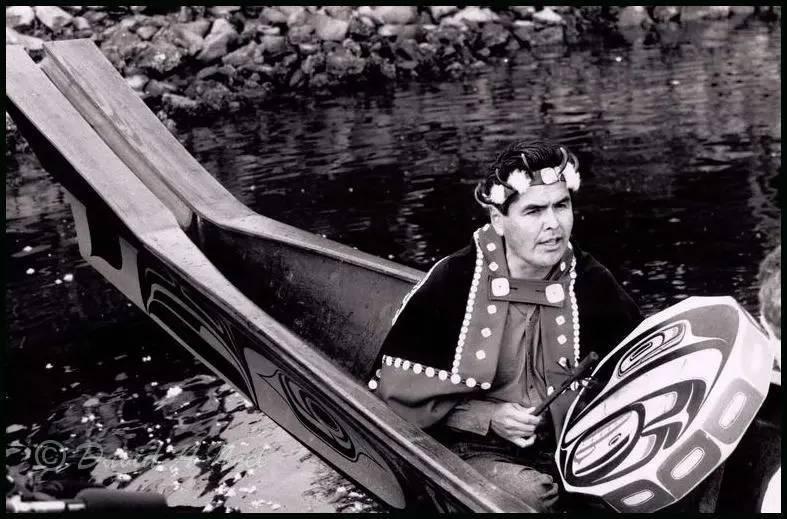 Robert Davidson singing with a hand drum in Bill Reid's canoe.